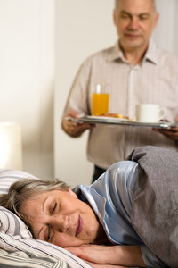 Loving senior husband serving breakfast to sleeping wife