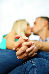 Loving young couple kissing at home. Focus on hands
