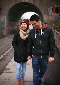 Loving young couple walking on a street smiling. Mixed race couple walking on sidewalk.