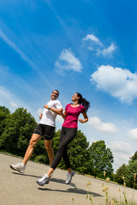 Low angle view of  happy couple running outdoors