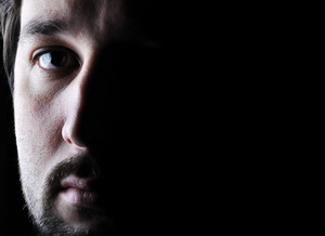 Low-key portrait - half face - sad and angry looking man
