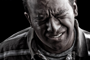 Low key portrait of a man suffering from extreme anguish pain or other hardship over a black background.