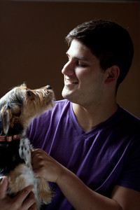 Low key portrait of a young man holding a cute mixed breed terrier dog isolated over a dark background.