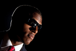 Low key portrait of an African American business man dressed in a suit and sunglasses standing in front of a dark black background.