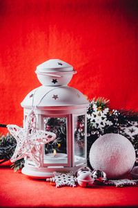 Magical white lantern is standing with beautiful white knit star on it and a fir tree branch and a snowball lying in front of it on a christmas red background. Christmas card with copy space.