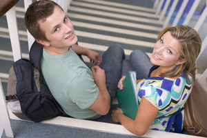 Male and female college students sitting on stairs