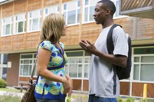 Male and female college students talking on campus