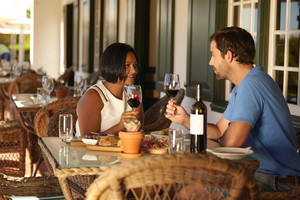 Male and female sitting at a restaurant holding glasses for wine and talking. Couple having a red wine at winery restaurant.