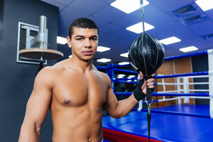 Male boxer standing in gym and looking at camera