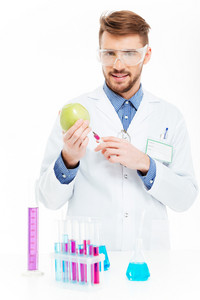 Male chemist doing injection of GMOs into apple isolated on a white background