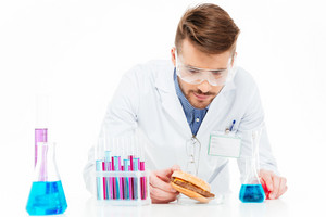 Male chemist making GMOs food isolated on a white background