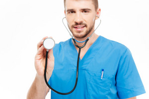 Male doctor holding stethoscope isolated on a white background. Focus on stethoscope