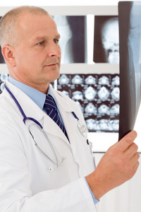 Male doctor standing at front of set x-ray looking