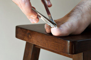 Male foot closeup as he clips his large toe nail.