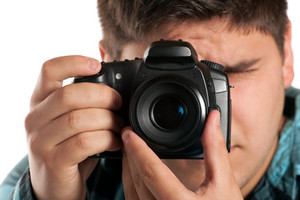 Male Photographer Shooting digital slr camera isolated on white.  Shallow depth of field.
