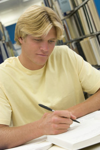 Male student working on report in library