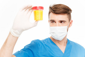Male surgeon with mask holding bottle of urine sample isolated on white background
