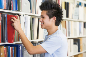 Male university student selecting book from library
