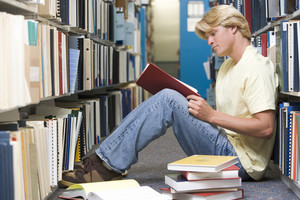 Male university student sitting on floor surrounded by books