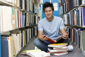 Male university student sitting on library floor surrounded by books