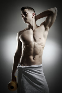 Male with towel holding dumbbell
