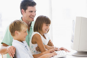 Man and two young children in home office with computer smiling