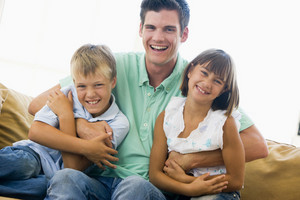Man and two young children in living room smiling