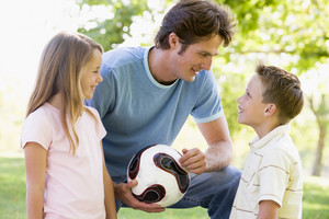 Man and two young children outdoors holding volleyball and smiling