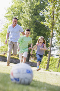 Man and two young children outdoors playing soccer and having fun