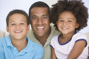 Man and two young children sitting in living room smiling