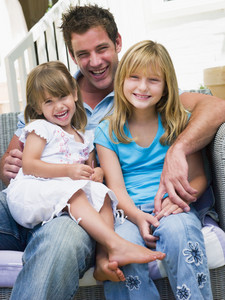 Man and two young girls sitting on patio smiling