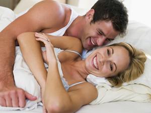 man and women awake in bed laughing