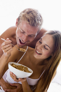 Man and women cuddling eating breakfast