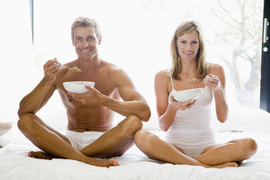 Man and women eating breakfast on a bed