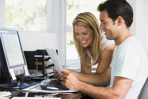 man and women reading a letter by the computer at home