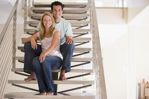 man and women sitting on stairs indoors