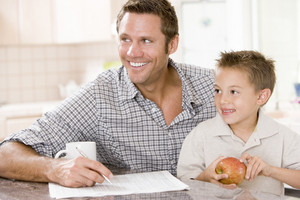 Man and young boy in kitchen with newspaper apple and coffee smiling