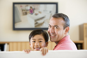 Man and young boy in living room with flat screen television smiling