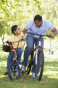 Man and young boy on bikes outdoors smiling
