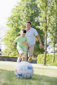 Man and young boy outdoors playing soccer and having fun
