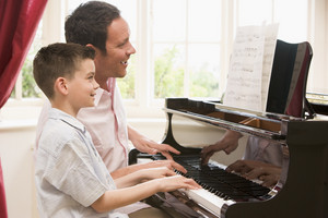 Man and young boy playing piano and smiling