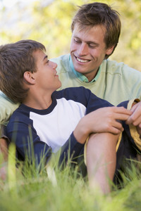 Man and young boy sitting outdoors smiling
