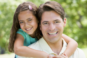 Man and young girl embracing outdoors smiling