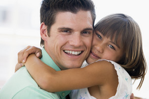 Man and young girl hugging and smiling