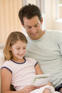 Man and young girl in living room reading book and smiling