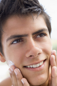 Man applying shaving cream smiling