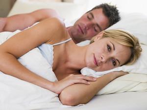 man asleep and women awake in bed