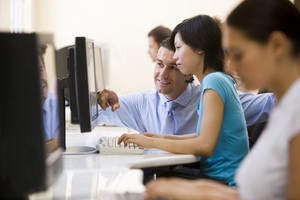 Man assisting woman in computer room smiling