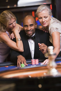Man at roulette table in casino surrounded by glamorous women