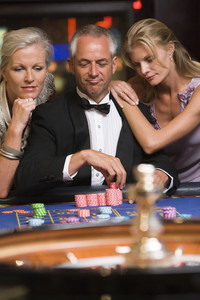 Man at roulette table surrounded by beautiful women